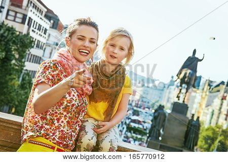 Happy Mother And Child Tourists In Prague Pointing In Camera