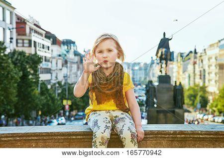 The spirit of old Europe in Prague. Portrait of modern child on Vaclavske namesti in Prague Czech Republic handwaving