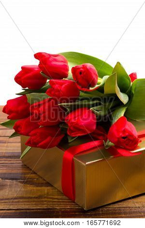 bouquet of red tulips and gift box on rustic wooden board.copy space