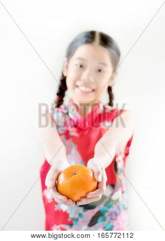 Blur of Smiling young asian girl standing on white background giving or showing perfect orange as a gift for get rich and good luck for happy chinese new year. Focus on orange.