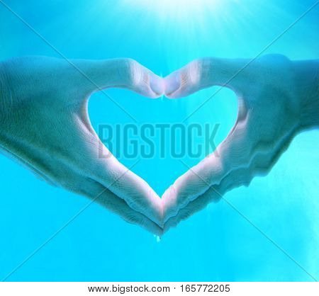 Hands of woman make heart shape sign unwater in swimming pool with clear blue water and sunrays on top for Happy valentines day concept and copy space.