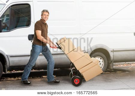A Smiling Delivery Man Pushing Parcels On Handtruck\ufffd\ufffdIn Front Of The Van