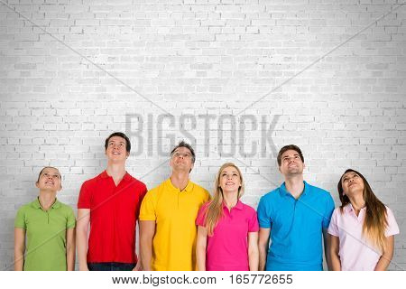 Group Of Diverse Happy People Standing Against A Wall Looking Up