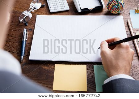 Close-up Of Businessperson Holding Pen On Blank Notebook At Wooden Desk In Office