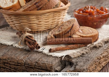 Tasty cake roll and jam on  a old wooden table. Rustic style