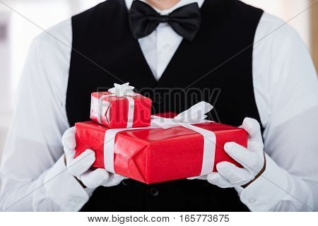 Close-up Of Waiter Wearing White Gloves And Holding Christmas Gift