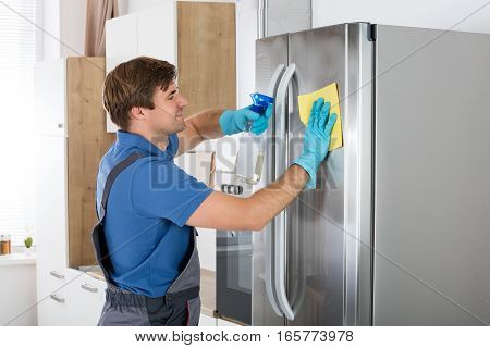Young Man Cleaning Stainless Refrigerator With Rag And Bottle Spray In Kitchen