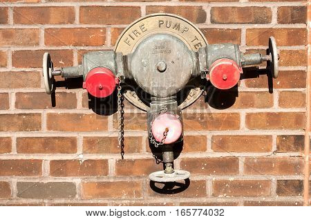 Fire hydrant with tree valves mounted on red brick house wall