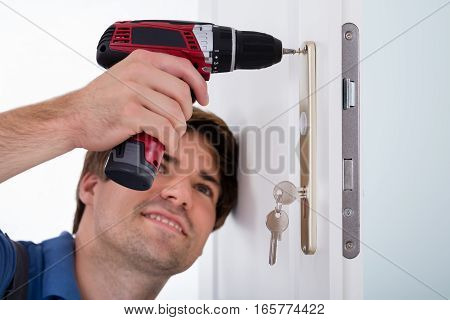 Close-up Of Smiling Happy Young Male Installing Door Lock On Door Using Wireless Screwdriver