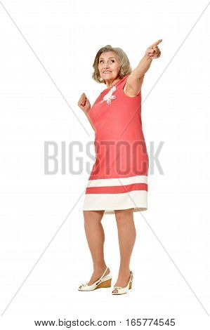 Elderly woman in dress pointing on white background
