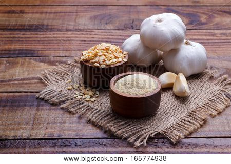 garlic cloves, bulb, flakes and powder on old wooden board