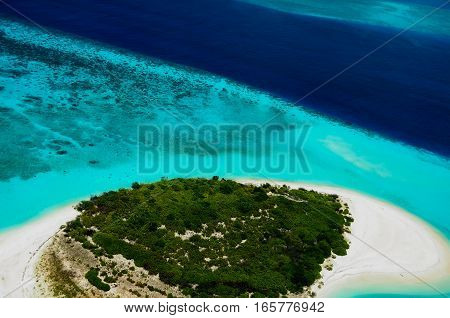 Aerial view to green desert Maldivian islland surrounded by blue ocean water
