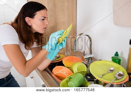 Young Woman Washing Plate In The Kitchen