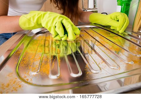 Close-up Of Woman Hand Cleaning Untidy Stainless Steel Sink In The Kitchen