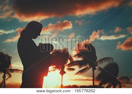 silhouette of loving mother with infant baby at sunset tropical beach