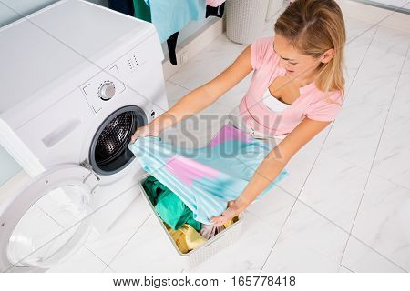 Angry Shocked Woman Looking At Stained And Bleached Clothes Near Washing Machine At Utility Room