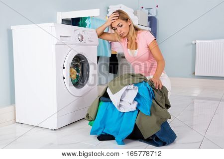 Unhappy Woman Showing Signs Of Fatigue Looking At Pile Of Clothes Near Washing Machine
