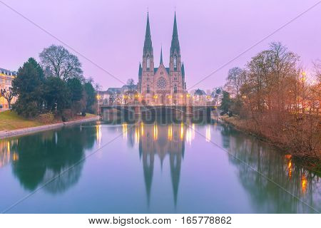 Picturesque foggy Reformed Saint Paul church with mirror reflections in the river Ile during morning blue hour, Strasbourg, Alsace, France