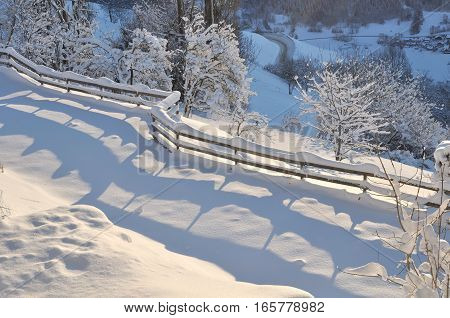 garden snowy closed by a wooden fence in mountain landscape