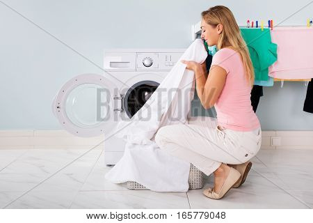 Woman Smelling Cleaned Clothes Near The Electronic Washer At Laundry Room