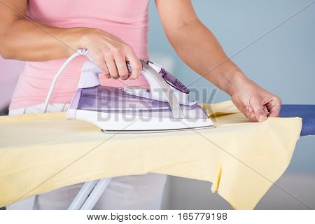 Laundry Services. Woman Hand Ironing Cloth On Ironing Board