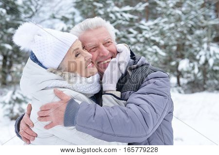 happy mature couple posing outdoors in winter