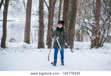 GRODNO BELARUS - JANUARY 15 2017. The boy in the winter forest carries skis.