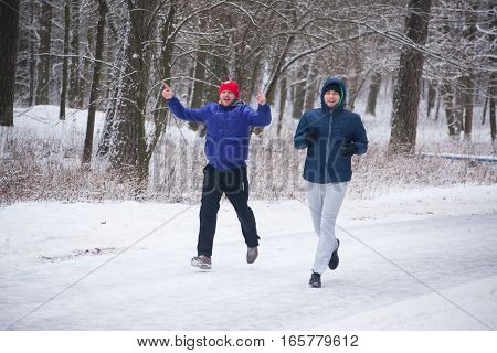 GRODNO BELARUS - JANUARY 15 2017. Two young men are engaged in a run in the winter forest.