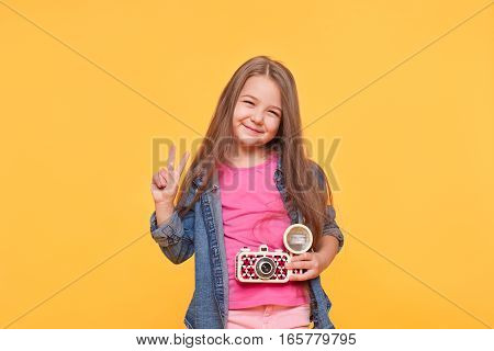 Young little girl photographer, holding a retro camera and showing peace sign isolated over yellow background
