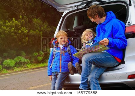 father with kids looking at map while travel by car, family car travel
