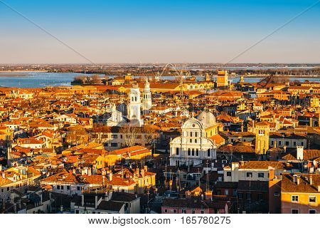Aerial view of Venice, Italy, at sunset with rooftops of buildings and warm sunlight.