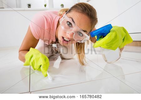 Close-up Of A Frustrated Young Woman Cleaning Floor With Brush At Home