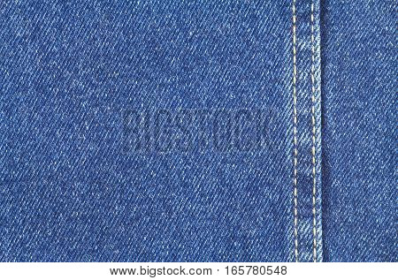 Texture of blue jeans fabric with yellow double stitching on right side close up