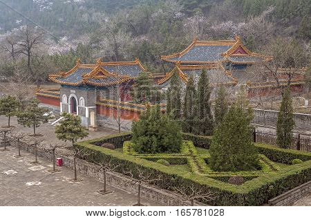 China; Beijing .Section of the Great Wall of China Tszyuyyunguan in Changping district crosses the river valley Guangou . Temple at the entrance to the fortress. The April foggy morning .