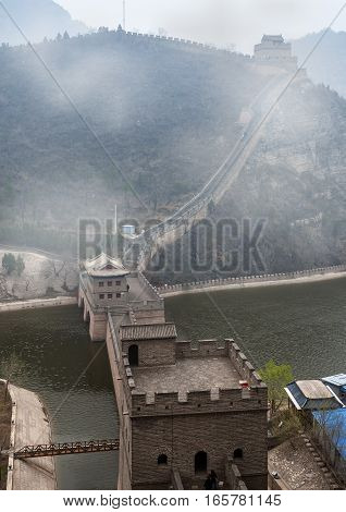 China; Beijing. Section of the Great Wall of China Tszyuyyunguan in Changping district crosses the river valley Guangou . Castle and bridge over the river. The April foggy morning .