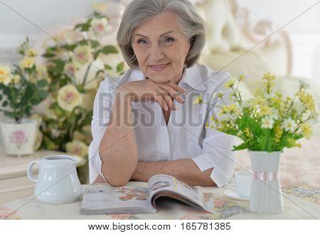 Portrait of a beautiful mature woman reading magazine