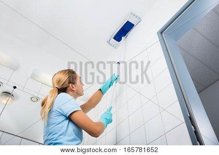 Cleaning Service Woman Cleaning The Ceiling Of The Bathroom With Mop At Home
