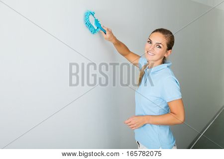 Young Woman Cleaning The Ceiling With Mop On The Corridor Of The Building