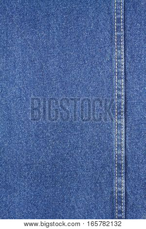Texture of blue jeans fabric with yellow double stitching
