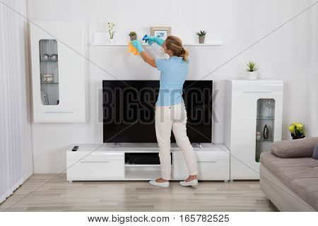 Young Woman Cleaning Furniture At Home With Spray Bottle And Cloth