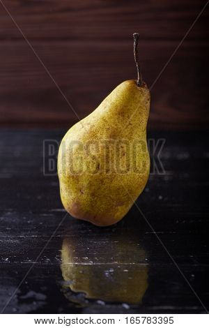 Single pear on wooden rustic background with reflection Minimal style. Vertical shot