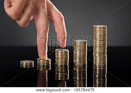 Close-up Of A Person Finger Walking Up Over Stack Of Coins Over Gray Background. Business Growth Concept