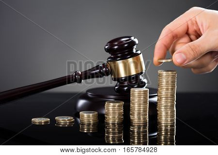 Close-up Of A Person Hand Stacking Coins In Front Of Mallet Over Gray Background