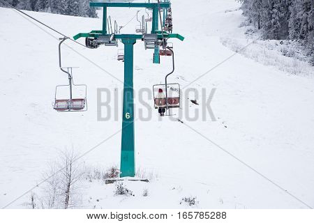 Skiers On Ski-lift In Snow Mountains At Winter Day. Cable Car Lift At Ski Resort
