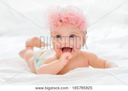 Cute happy little baby girl with big blue eyes wearing a pink bow.