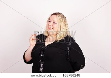 Very complete cheerful woman in a black dress with glasses in hand.