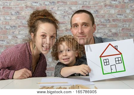 happy family child holding paper with drawing a house