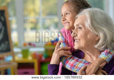 Portrait of smiling grandmother and granddaughter hug and look at the distance