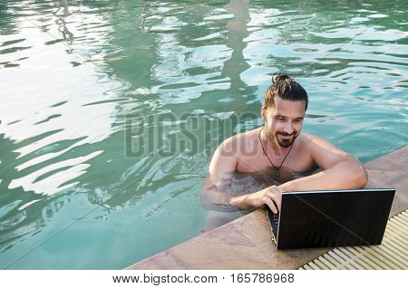 Workplace at the resort. Young man with a phone and a laptop in the swimming pool. Freelancer at work.