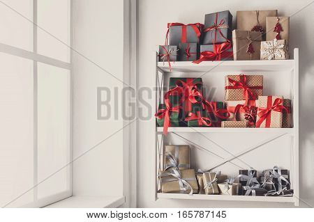 Colorful gift boxes wrapped in paper at white shelves near window. Any holiday background with copy space. Christmas, birthday or valentine concept. High key